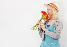 Blond kvinna med lukta blommor för sunhatt Royaltyfri Foto
