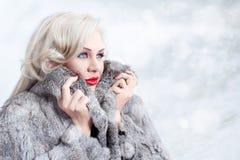 Blond kvinna med pälslaget i snön royaltyfria foton