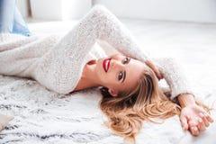 Blond kvinna med röd läppstift som inomhus ligger på golvet arkivfoton