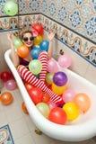 Blond kvinna med solglasögon som spelar i hennes badrör med ljusa kulöra ballonger Sinnlig flicka med vita röda randiga strumpor Royaltyfria Bilder