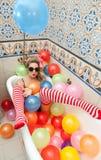 Blond kvinna med solglasögon som spelar i hennes badrör med ljusa kulöra ballonger Sinnlig flicka med vita röda randiga strumpor Fotografering för Bildbyråer