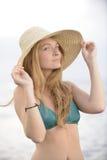 Blond kvinna med sunhat på stranden Arkivbild