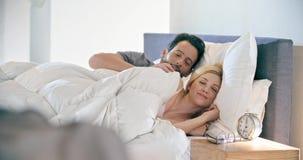 Blond kvinna och man som ler, kramar och vilar Koppla ihop den förälskade morgonvaken upp hemma in sovrum caucasian stock video