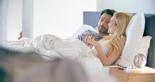 Blond kvinna och man som talar efter sömn Koppla ihop den förälskade morgonvaken upp hemma in sovrum Caucasian flickvän och lager videofilmer