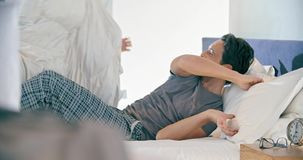 Blond kvinna och manskämtande- och kuddestridighet Koppla ihop den förälskade morgonvaken upp hemma in sovrum Caucasian flickvän stock video