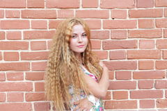 Blond kvinna- och tegelstenvägg Arkivbilder