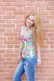 Blond kvinna- och tegelstenvägg Royaltyfria Bilder