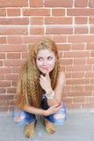 Blond kvinna- och tegelstenvägg Royaltyfria Foton