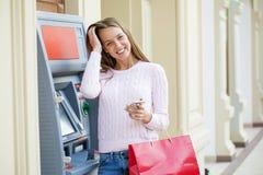 Blond kvinna på bakgrunden i köpcentret ATM fotografering för bildbyråer