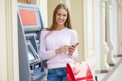 Blond kvinna på bakgrunden i köpcentret ATM royaltyfria bilder