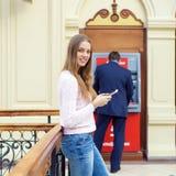 Blond kvinna på bakgrunden i köpcentret ATM royaltyfri bild