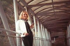 Blond kvinna på bron genom att använda smartphonen Royaltyfria Bilder
