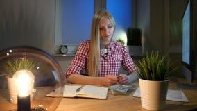 Blond kvinna på skrivbordet som ser bitcoin Härligt ungt blont kvinnligt sammanträde på arbetsplatsen med datoren och öppnar arkivfilmer