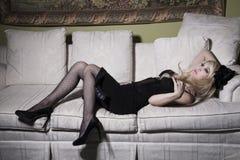 Blond kvinna på sofaen Arkivbild