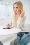 Blond kvinna på tabellen med minnestavladatoren Royaltyfria Bilder