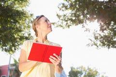 Blond kvinna som använder hennes resehandbok arkivfoton