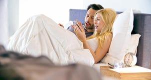 Blond kvinna som använder smartphonen med pojkvännen i säng på morgonen Koppla ihop den förälskade morgonvaken upp hemma in bedro lager videofilmer