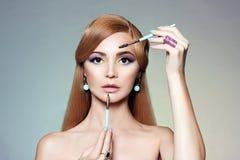 Blond kvinna som applicerar färgsmink royaltyfri foto