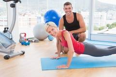 Blond kvinna som arbetar på övningen som är matt med hennes instruktör Royaltyfria Bilder