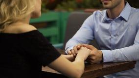 Blond kvinna som bekänner hennes mjuka förälskelse till älsklingmannen, romantiskt datum i kafé stock video