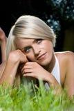 Blond kvinna som dagdrömmer, medan lägga på gräs fotografering för bildbyråer