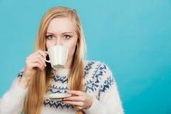 Blond kvinna som dricker den varma drinken fr?n koppen arkivbilder