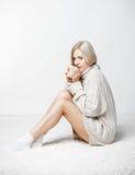 Blond kvinna som dricker ett lock av te Fotografering för Bildbyråer