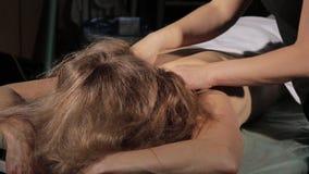 Blond kvinna som får huvudmassage i brunnsort östlig medicinconcepte, tai-massage arkivfilmer