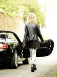 Blond kvinna som får in i sportbilen royaltyfri bild