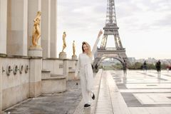Blond kvinna som går på Trocadero den fyrkantiga near förgyllda statyer och Eiffeltorn Arkivfoton