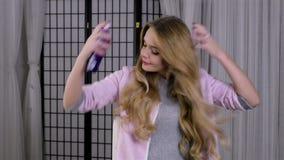 Blond kvinna som gör hennes hår spritz hårspray arkivfilmer