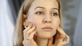 Blond kvinna som gör själv-massagen som i regeringsställning anti--åldras ansikts- massage daglig framsidakondition och framsidab stock video