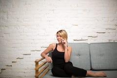 Blond kvinna som har mobiltelefonkonversation medan henne som kopplar av på soffan i hemmiljö royaltyfri bild