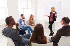 Blond kvinna som i regeringsställning gör presentation Fotografering för Bildbyråer