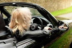 Blond kvinna som kör bilen fotografering för bildbyråer