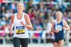 Blond kvinna som kör den sista elasticiteten på Stockholm Stadion Royaltyfri Fotografi