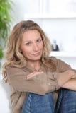 Blond kvinna som kopplar av på sofaen Royaltyfria Foton