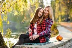 Blond kvinna som kramar hennes nätta dotter båda som ler royaltyfria bilder