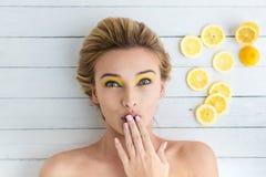 Blond kvinna som lägger bredvid skivor av citronen arkivfoto