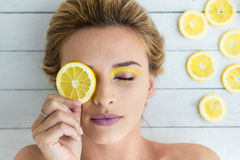 Blond kvinna som lägger bredvid skivor av citronen arkivbild