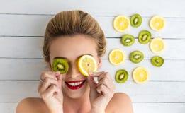Blond kvinna som lägger bredvid skivor av citronen och kiwin Royaltyfria Bilder
