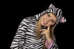 Blond kvinna som ler bärande kattpyjamas som ner sitter royaltyfria foton