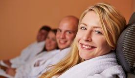 Blond kvinna som ler i brunnsort Royaltyfri Foto