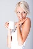 Blond kvinna som ler rymma en kopp royaltyfri fotografi