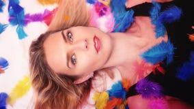 Blond kvinna som ligger ner omgivet av färgrika fjädrar Arkivfoto