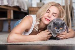 Blond kvinna som ligger på golv med katten Royaltyfri Foto