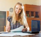 Blond kvinna som läser det finansiella dokumentet Arkivbild