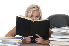 Blond kvinna som plirar över boken Arkivbilder