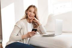 Blond kvinna som poserar att sitta inomhus hemma genom att använda den bärbar datordatoren och mobiltelefonen arkivbild