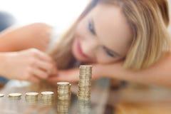 Blond kvinna som räknar myntkolonner Royaltyfri Fotografi